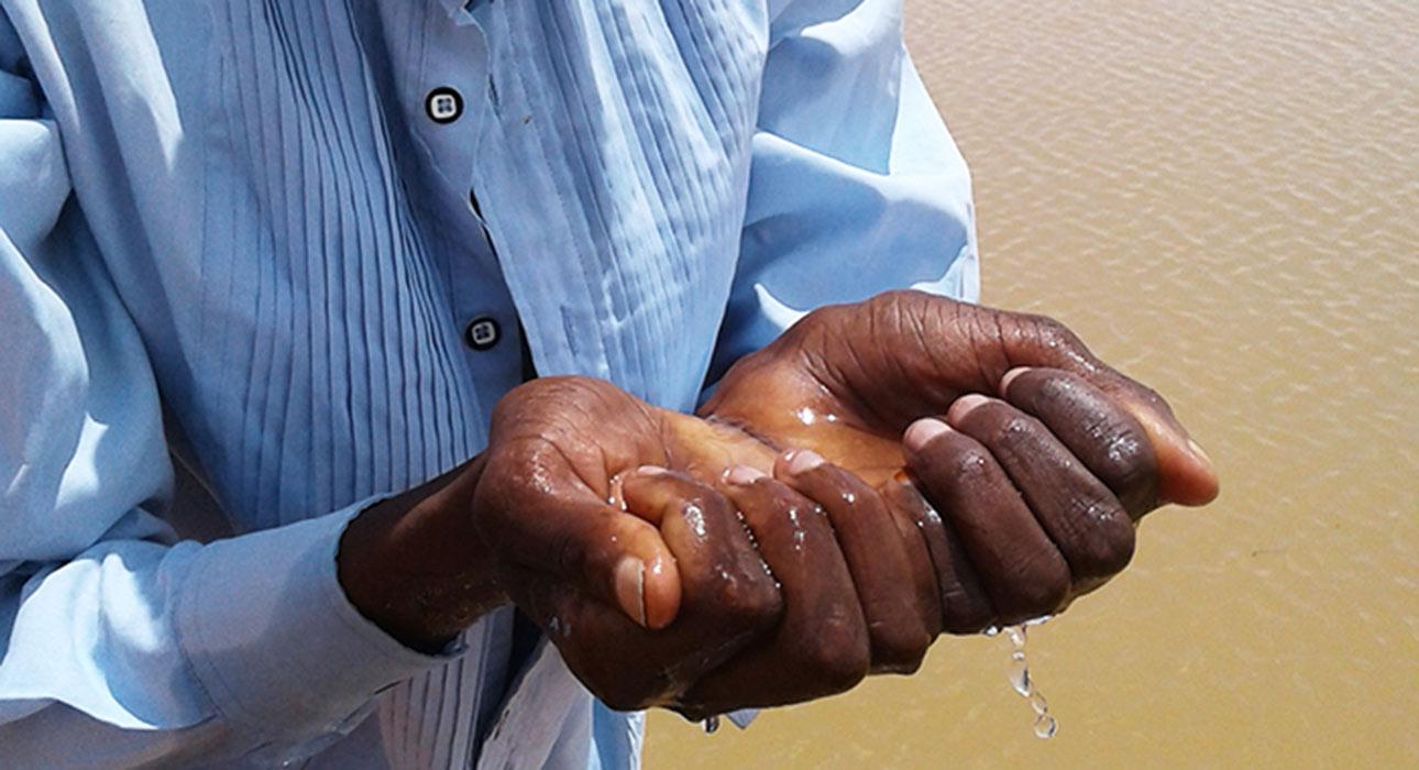 Miehen kädet täynnä vettä sadevedenkeruualtaan luona.