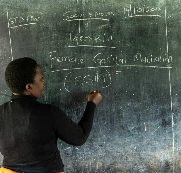 Opettaja Keniassa kirjoittaa liitutaululle.