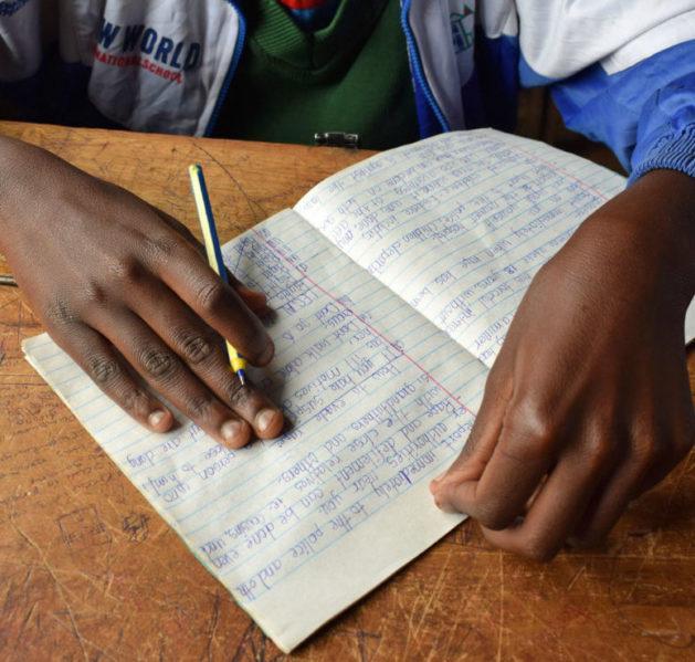 Lapsi kirjoittaa muistiinpanoja silpomisen vastaisella turvaleirillä
