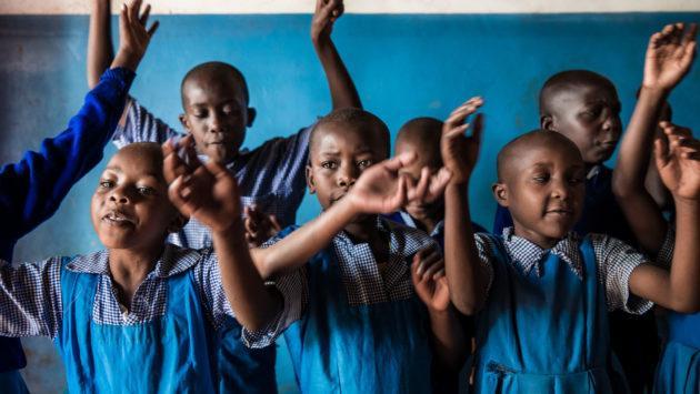 Lapset laulavat silpomisen vastaista laulua turvaleirillä Keniassa.