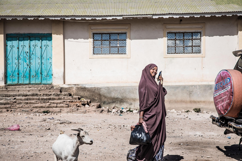 Henkilö puhuu puhelimeen ja katsoo hymyillen kameraan Somalimaassa