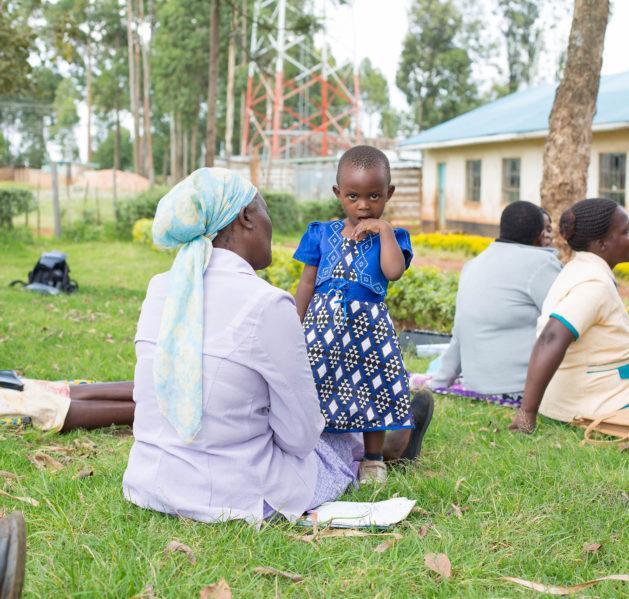 Isoäiti ja lapsi nurmikentällä muiden naisten kanssa