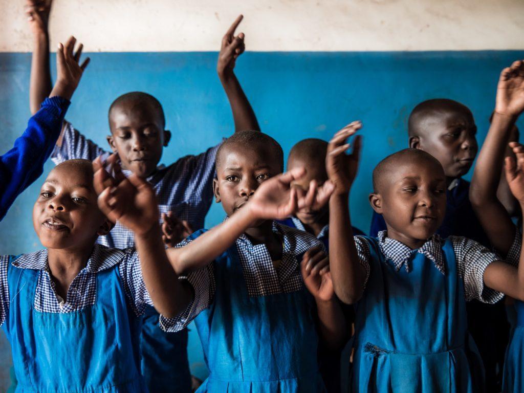 Ryhmä oppilaita leikkii ja laulaa Keniassa
