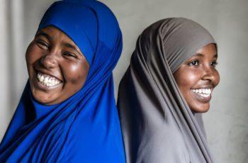 Lähikuva jossa kaksi ihmistä seisoo selät vastakkain hymyillen