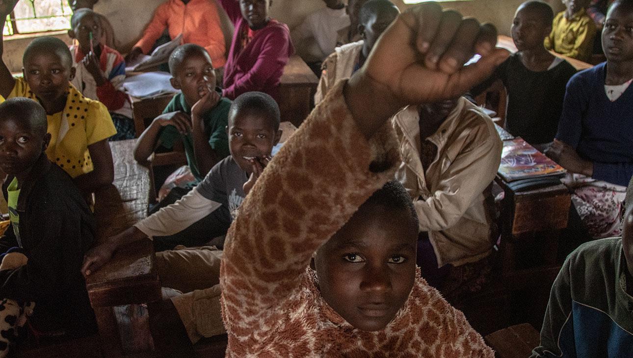 Rael Kemunto etualalla käsi ilmassa. Taustalla luokkahuoneessa muita kisii-yhteisön lapsia. Valokuvan on ottanut Nyasha Kadandara.