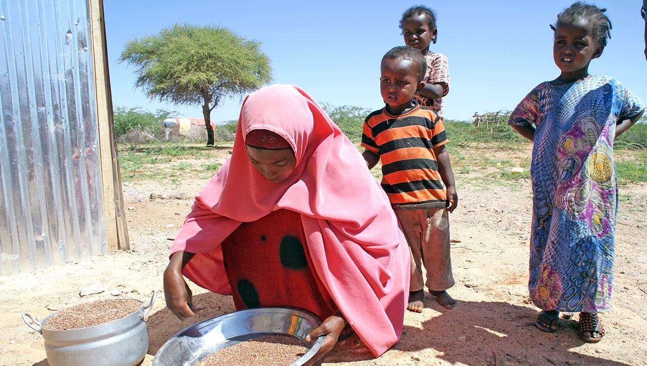Äiti laittaa Somalimaassa ulkona ruokaa kyykyssä. Kuva Anna-Sofia Joro