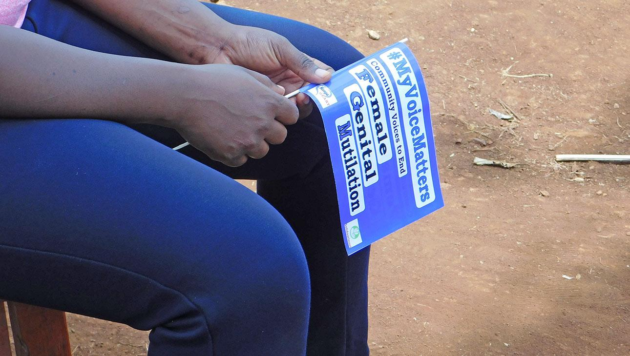 Tyttöjen silpomista vastustava kannatuslippu naisen käsissä