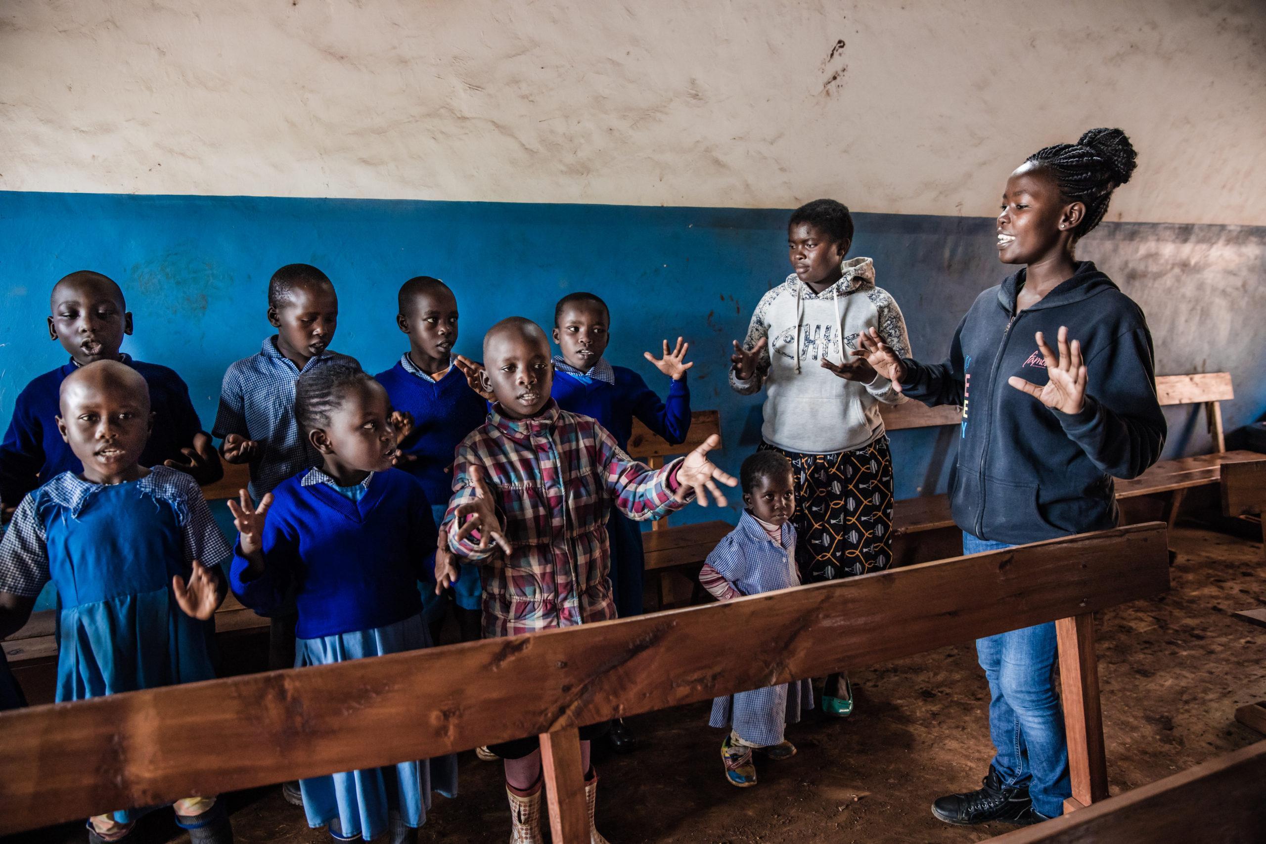 Tarinansa kertonut Neema Nyaundi on kuvassa oikealla laulattamassa koululaisia. Lapset pääsevät käsittelemään vaikeaa silpomisaihetta ikätasoonsa sopivalla tavalla laulun keinoin. kuva: Meeri Koutaniemi