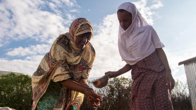 Äiti ja tytär pesemässä käsiä Somalimaassa kotitalon pihalla.