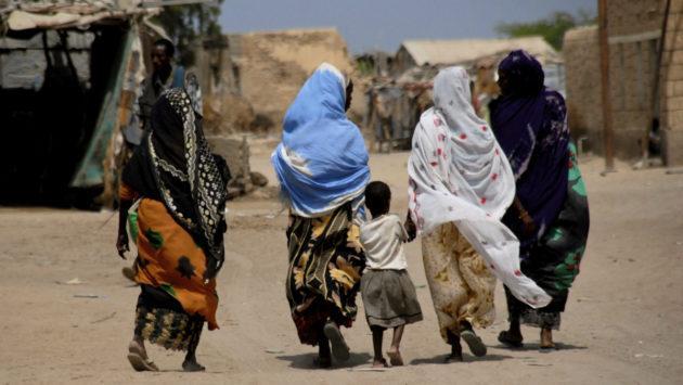 Aikuisia ja lapsi takaa päin kuvattuna kävelemässä ulkona Somalimaassa.