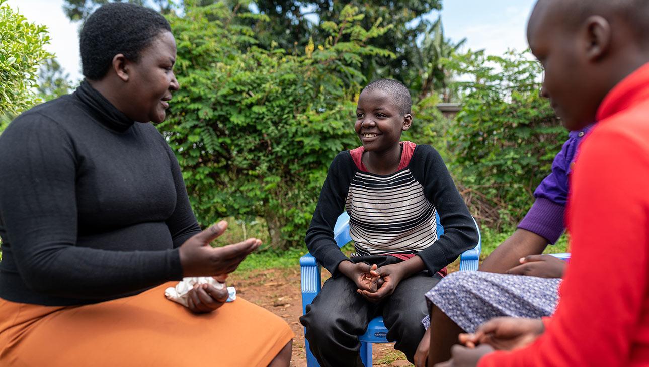 Opettaja ja vapaaehtoinen Alice kertomassa oppilaalle silpomisen haitoista.