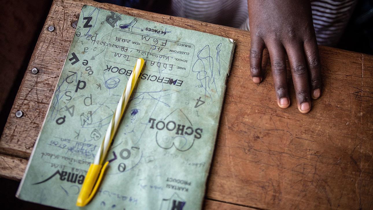 Synkkä kuva, jossa on tytön kouluvihko ja pieni käsi