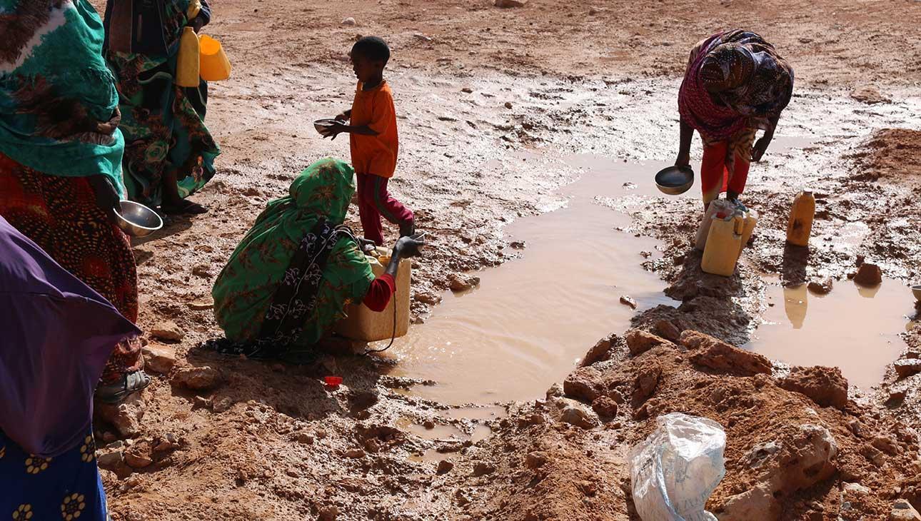 Ihmiset keräämässä vettä talteen lyhyen sateen jälkeen.